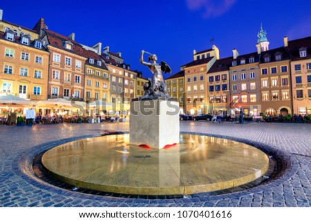 Night view of the bronze statue of Mermaid on the Old Town Market Square of Warsaw, surrounded by colorful old houses, Poland. #1070401616
