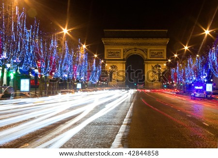 Night view of the Champs-Elysees with Christmas illumintation and the Arc de Triomphe in Paris, France - stock photo
