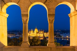 Night view of the famous Hungarian Parliament across the river Danube in Budapest, as seen through the arches of Buda Castle Fishermen Bastion. Long exposure.