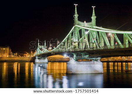 Night view of the illuminated Liberty Bridge (or Freedom Bridge) in Budapest, Hungary. Connects Buda and Pest across the River Danube with some place for text on the left