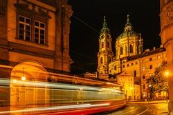 Night view of the illuminated St Nicolas church, Malostranske namesti,Prague,Czech republic.Lesser Town of Prague.Long exposure lights. Movement of tram. Traffic lights.Night city scene.Travel concept