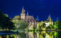 night view of the illuminated vajdahunyad castle in varosliget parc in budapest.