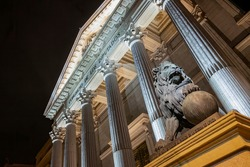night view of the main facade of the Palacio de la Cortes, palace of courts, seat of the Congress of Deputies in Madrid, Spain, with one of its iconic bronze lions in the foreground