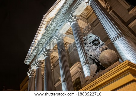 night view of the main facade of the Palacio de la Cortes, palace of courts, seat of the Congress of Deputies in Madrid, Spain, with one of its iconic bronze lions in the foreground Foto stock ©