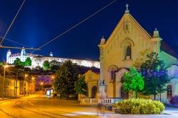 Night view of the St. Stephan Capuchin church and Bratislava castle, Slovakia.