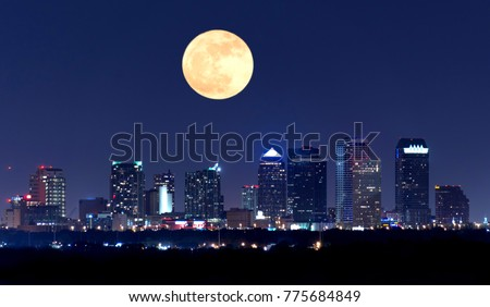 Night view of the Tampa Florida skyline showing skyscrapers with lights and a huge full moon in the sky over the buildings.