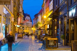 Night view of Torun streets and building illuminated at dusk, old town in Poland