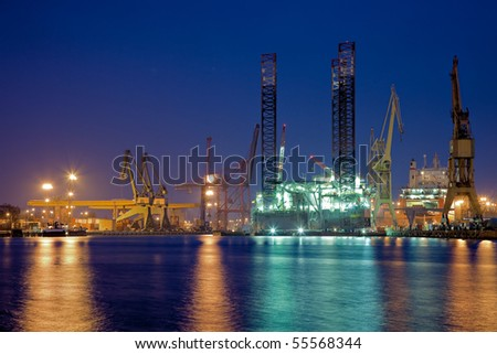 Night view of yards offshore drilling in the background. - stock photo