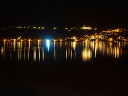Night view of Zell am Zee on a lake in Austria. Landscape on the background of the dark sky and mountains during the summer vacation.