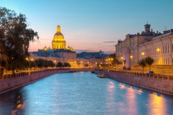 Night view on illuminated Moyka River and Saint Isaac's Cathedral behind buildings, St. Petersburg, Russia