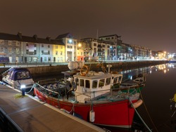 Night view on row of buildings and fishing boats in Galway Docks