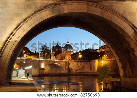 Night view on Saint peter cathedral of the Vatican, Rome, Italy, seen from under a bridge over the tiber river