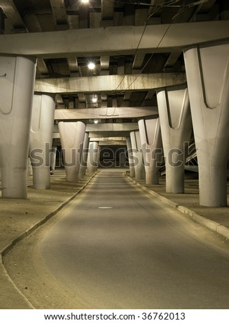 Night view on the road under concrete road bridge with column