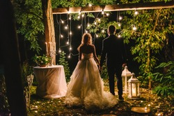 Night wedding ceremony with candles, lanterns and lamps on tree. Bride and groom holding hands on background of bulb lights, back view. Beautiful young couple standing under tree at night, copy space
