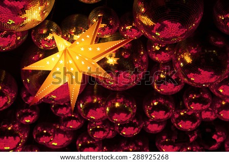 Nightclub red disco balls and glowing gold color star in colorful festive lights in dance club