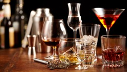 Nightlife concept with assorted alcoholic beverages arranged on a wooden bar counter with bottles of alcohol and utensils in a close up view