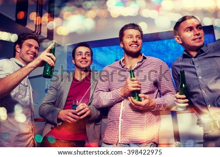 nightlife, party, friendship, leisure and people concept - group of smiling male friends with beer bottles drinking and pointing finger to something at nightclub