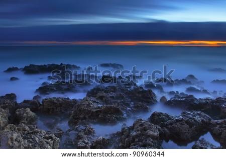 Nightly Seascape with rocky beach