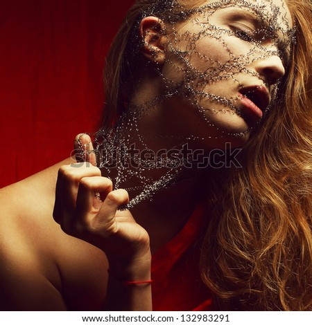 Nightmare of a young glamorous red-haired (ginger) woman in red cloth. Wire on a face. Studio shot