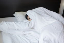 Nightmare or bad dream,Woman scared and peeking from blanket in bedroom