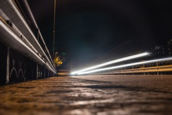 Nightphoto of a road with carlight going by slowshutter