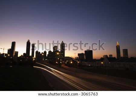 Nightscape of Atlanta, Georgia skyline with blurred automobile lights on highway.