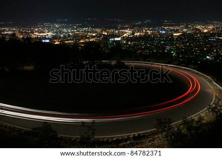 Nighttime, long exposure of car lights around hairpin curve on mountain road with city lights gleaming below.