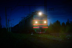 Nighttime shot of an electric train with light crossing the Russian countryside near Murmansk, Russia.