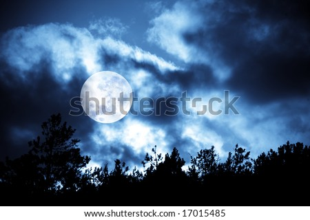 Nighttime sky with moon and clouds and trees silhouettes. Ideal for background.