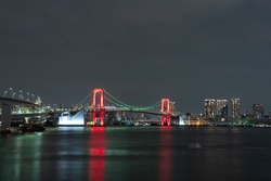 Nightview of Rainbow Bridge illuminated in red as a sign of Tokyo Alert, coronavirus alert for Tokyo area, in Odaiba Japan.