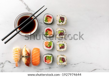 Nigiri sushi, maki rolls and soy sauce on a white stone background and chopsticks on the side. Traditional Japanese food, top view, copy space.