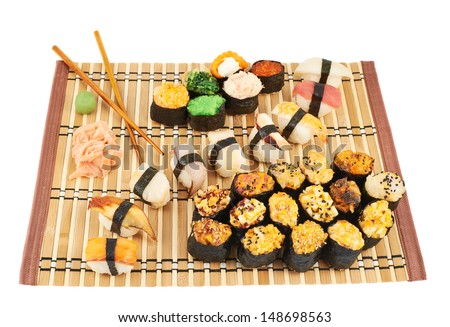 Nigirizushi and baked sushi composition on a bamboo mat isolated over white background