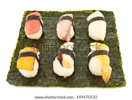Nigirizushi sushi with a chopsticks composition over nori sheet isolated over white background
