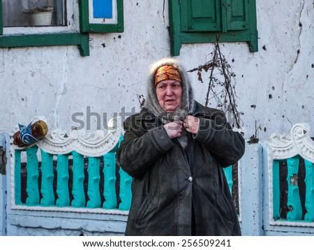 NIKISINO, UKRAINE - Feb 27, 2015: Middle-aged women stay near her ruined house in the village Nikishino, Donetsk region, Ukraine. - Village Nikishino located 20 km from Debaltseve,