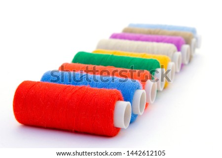 Nine brightly colored spools of threads for sewing on white background #1442612105