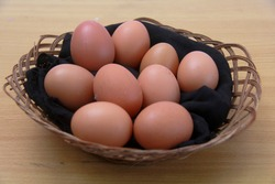 nine chicken eggs on a black cloth in a basket, and on a board table.