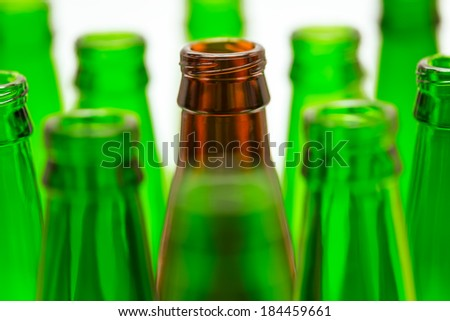 Nine green and one brown bottles. Central brown bottle neck in focus.
