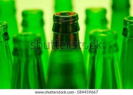 Nine green and one brown bottles shot with green light. Central brown bottle neck in focus.
