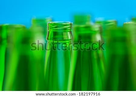 Nine green bottle necks on blue background, in center one bottle in focus.