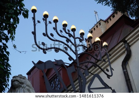 nine-lamp candelabrum used in contemporary Jewish temples, stay on street fence. Hanukkah menorah of the Jewish festival of Channukah. #1481611376