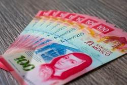 Nine Mexican 100 pesos new bills over a wood texture