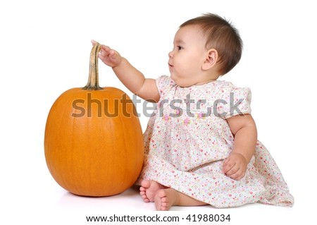 nine-month girl with her finger on a pumpkin stem, isolated on white background