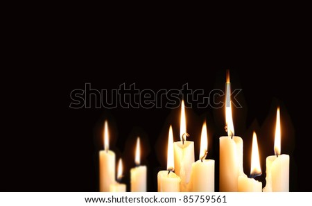 Nine ordinary lighting candles on black background with free space for your text