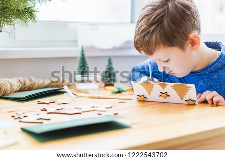 Nine years boy preparing christmas greeting cards for grandparents. Handmade Christmas gift ideas