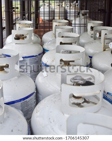 Nineteen propane cylinder tanks staged in metal cage ready for sale.   Сток-фото ©