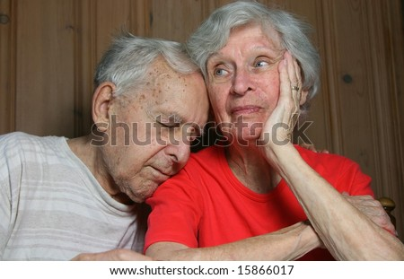 ninety year old couple looking extremely bored