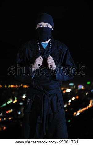ninja assasin hold katana samurai old martial weapon swordat night with city lights in background