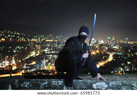 ninja assasin hold katana samurai old martial weapon swordat night with city lights in background - stock photo