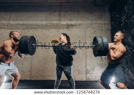 ninstandart unusual kind of sport. obese girl having a snack while training with barbell #1258768276