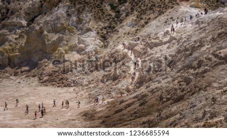 Nisyros, Greece - September 5, 2018: Group of tourists follow the road to the center of vulcano Stefanos  #1236685594